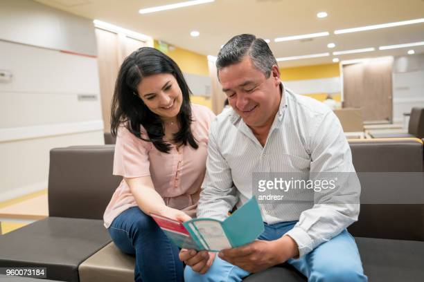 couple at the waiting room of a hospital looking at a brochure both very happy - brochure stock pictures, royalty-free photos & images