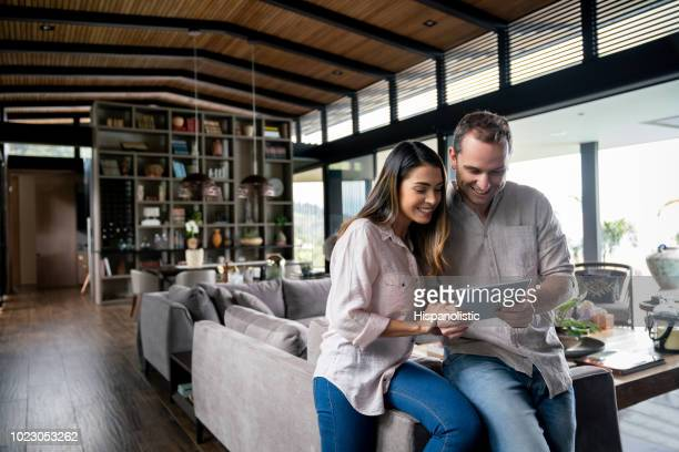 Couple at their modern and beautiful apartment looking at something on tablet
