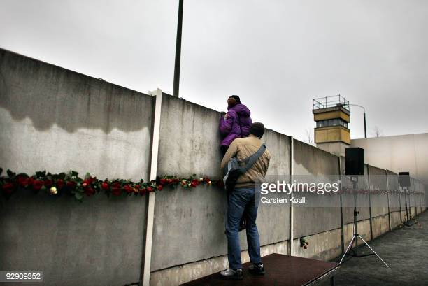 A couple attempts to peek through cracks and among roses left by visitors in a stillexisting section of the Berlin Wall into the socalled 'death...
