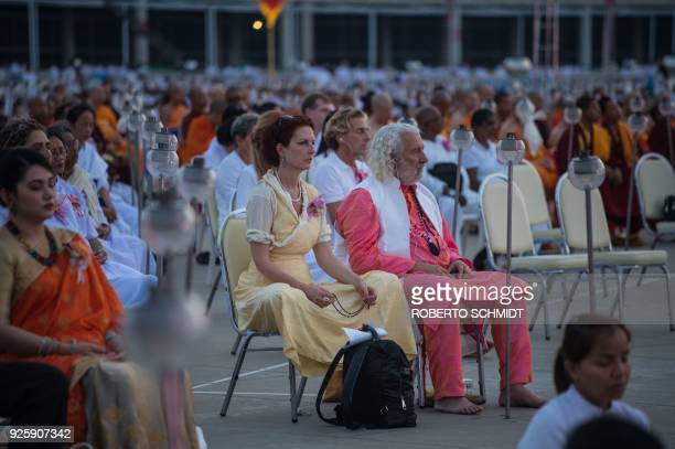 A couple attends the evening prayers during Makha Bucha Day celebrations at Wat Phra Dhammakaya temple near Bangkok on March 1 2018 Makha Bucha Day...