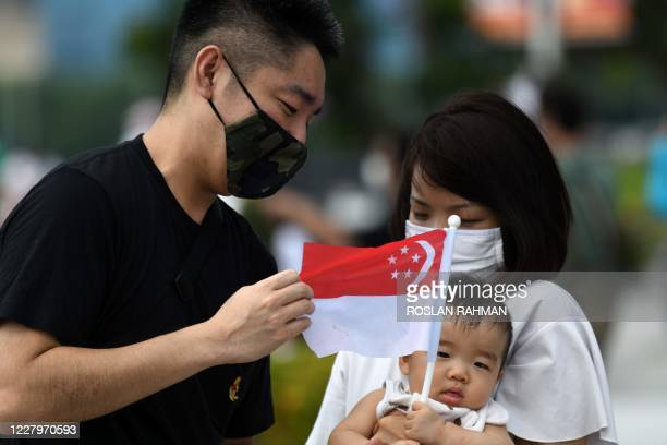 Couple attends to their child as the infant holds the Singapore national flag at the Merlion Park to mark the 55th National Day celebrations in...