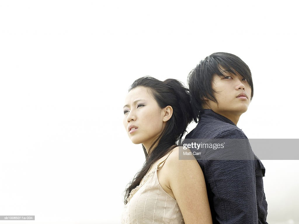 Couple back to back against white sky : Foto stock