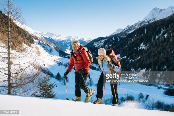 Couple backcountry ski above Swiss village after fresh snow