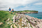 Couple backpacker travelers walk on ocean rocky coast