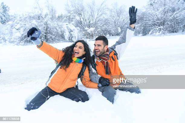 Couple backpackers having fun in snow forest