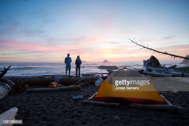a couple backpacking and camping along washintons remote coast. - washington state stock pictures, royalty-free photos & images