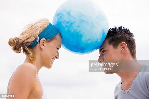Couple balancing beach ball between their heads