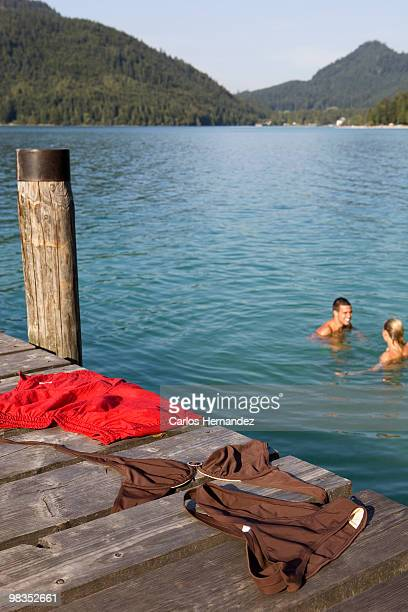 a couple bathing naked in a lake - dressed undressed stock-fotos und bilder