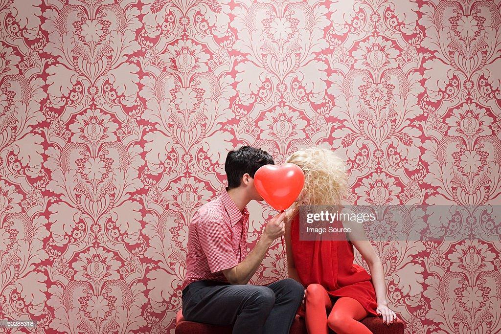 Couple behind heart shaped balloon : Stock Photo
