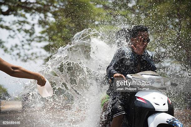 couple being splashed by a bucket of water while riding a motorbike on a road in Myanmar during Thingyan Water Festival, Myanmar's traditional New Year Festival, in April 2016