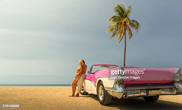 Couple beside Convertible on beach