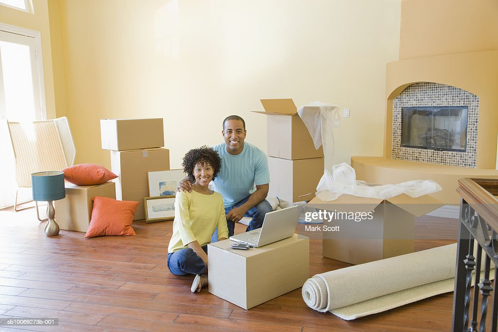 Couple between boxes in unfurnished room, portrait : Stockfoto
