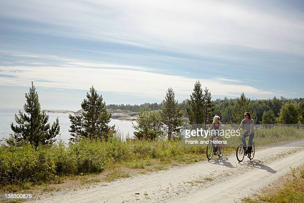 couple bicycling on rural dirt path - sweden stock pictures, royalty-free photos & images