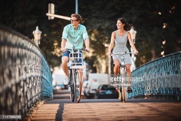 日没時に橋を渡るカップルバイク - フライブルク・イム・ブライスガウ ストックフォトと画像