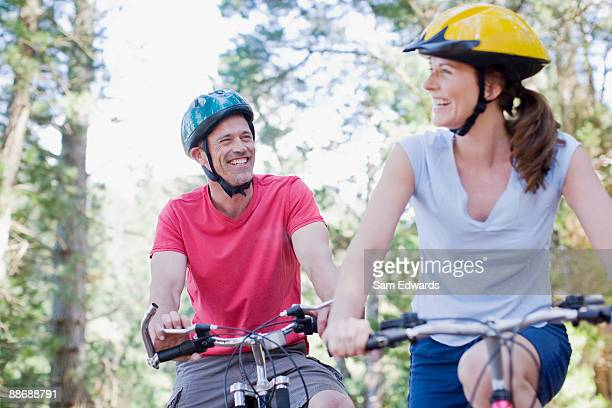 couple bike riding in forest - sports helmet stock pictures, royalty-free photos & images