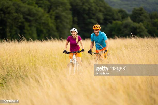 couple biking through dry grass - mid adult couple stock pictures, royalty-free photos & images
