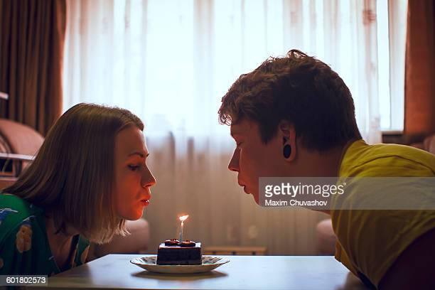 Couple blowing birthday candle on cupcake