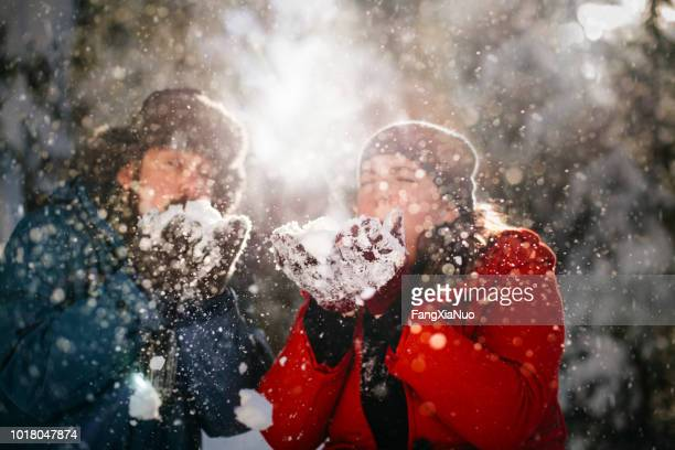 Couple blowing snow from hands in winter