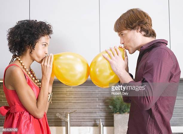 Couple blowing up balloons