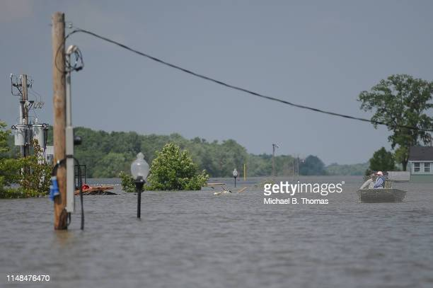 A couple boats up what would be a city street as floodwaters rise on June 7 2019 in Grafton Illinois Residents along Mississippi river are bracing...