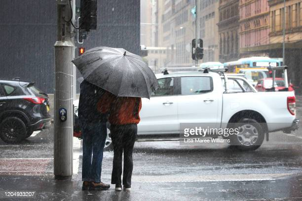 A couple brave heavy rain and strong winds along Park Street on February 08 2020 in Sydney Australia The Bureau of Meteorology has forecast heavy...