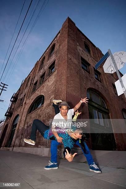 Couple breakdancing in urban area