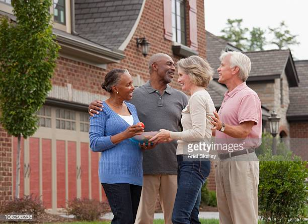 couple bringing food to new neighbors - welcoming guests stock photos and pictures