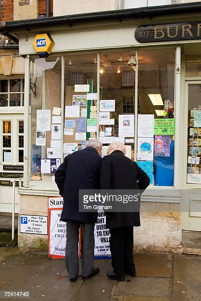 Couple browse the window of a newsagent's shop at Burford in the Cotswolds United Kingdom