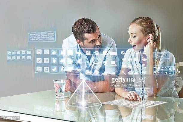 Couple browsing apps on their touch screen table
