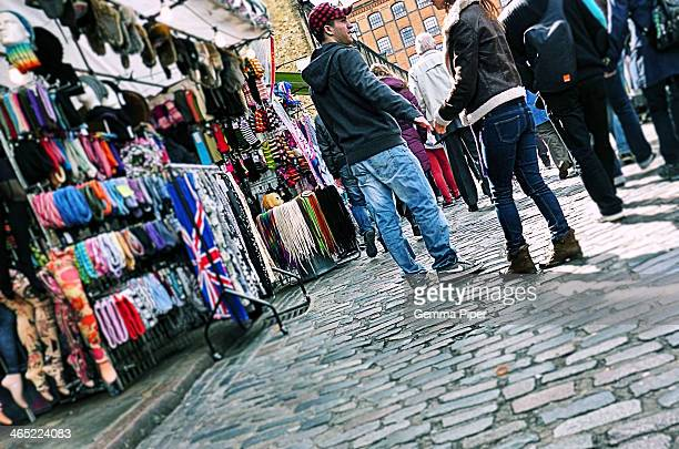 Couple browsing through the brightly coloured market stalls in the popular shopping and tourist hotspot, Camden.