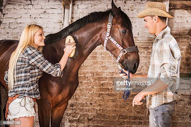 Couple brushing a horse in a barn.