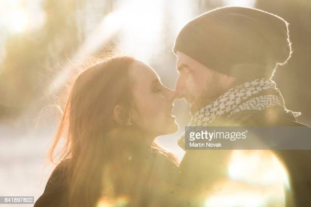 Couple brushing nose to nose outdoors
