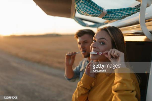 couple brushing teeth at camper van in rural landscape at sunset - camping stock-fotos und bilder