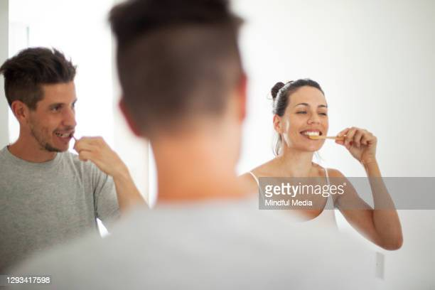 couple brushing teeth in bathroom - 30 39 years stock pictures, royalty-free photos & images