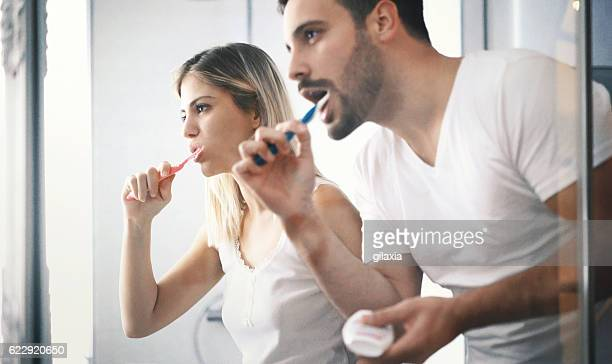 Couple brushing teeth in the morning.