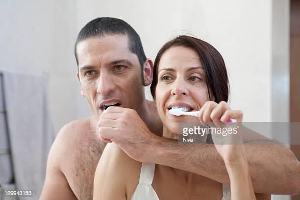 Couple brushing their teeth in bathroom