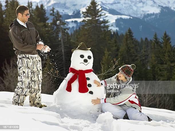 Paar bauen einen Schneemann