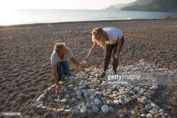 couple build fish stone artwork at beach, sunrise - fish love stock photos and pictures