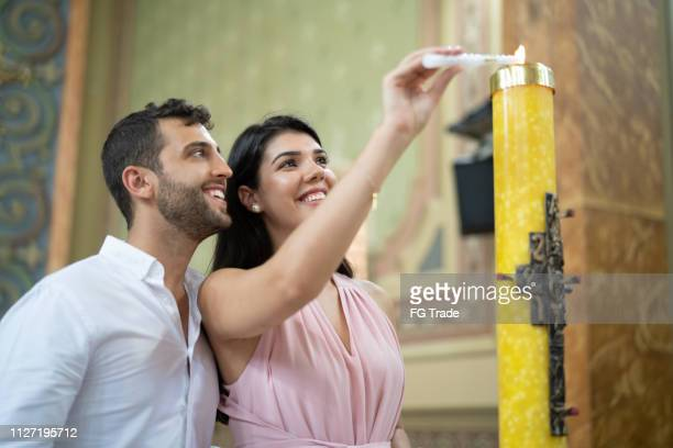 couple burning candle in a religious celebration - catholicism stock pictures, royalty-free photos & images