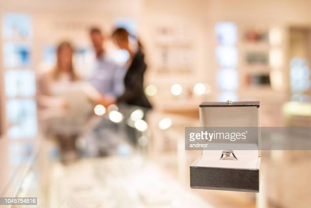 couple buying an engagement ring at a jewelry store - jewelry store stock pictures, royalty-free photos & images