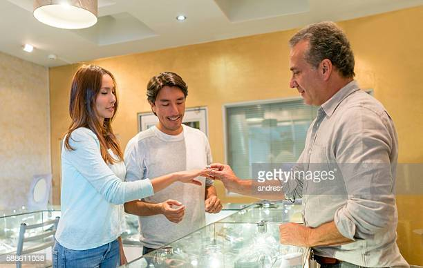 couple buying an engagement ring - jewelry store stock pictures, royalty-free photos & images