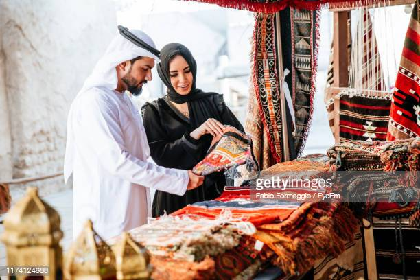couple buying clothing at market - abu dhabi stock pictures, royalty-free photos & images