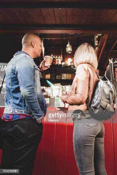 Couple buying coffee from food cart in city