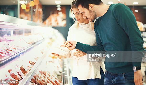 couple buying fresh meat in supermarket. - meat stock pictures, royalty-free photos & images