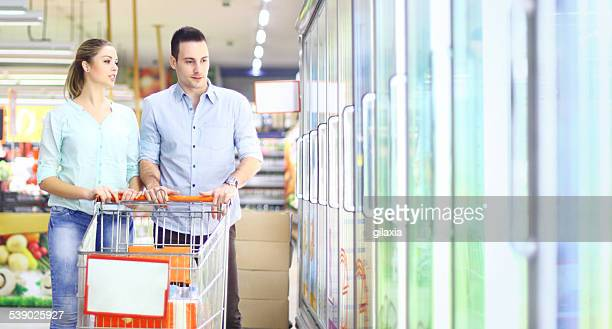 Couple buying frozen food in supermarket.