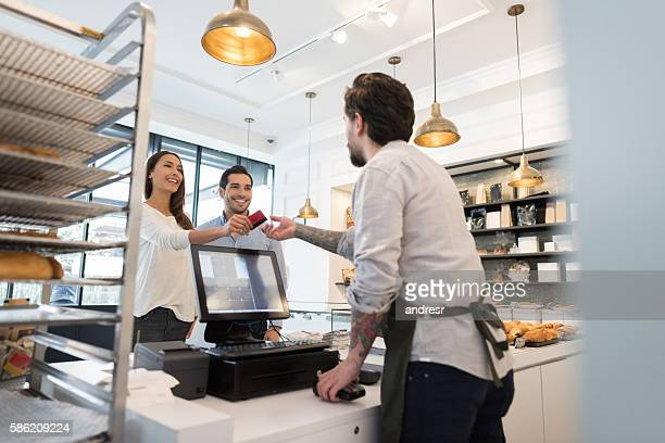 couple buying goods at the bakery - cash register stock pictures, royalty-free photos & images