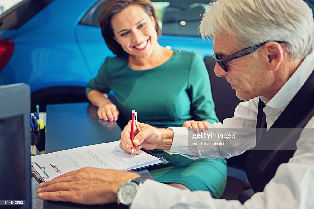 Couple buying new car and signing the contract : Stock Photo