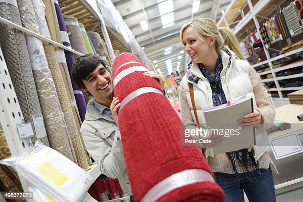 Couple buying red rug in shopping store