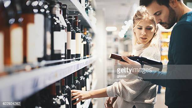 Couple buying some wine at a supermarket.