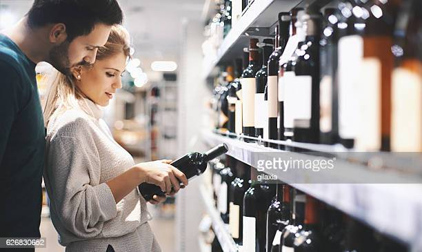 Couple buying wine in supermarket.